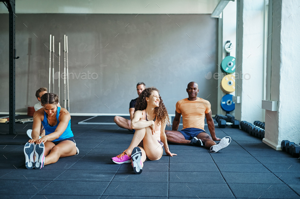 People laughing together on a gym floor after working out - Stock Photo - Images