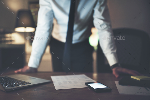 Worker standing at desk with papers and gadgets - Stock Photo - Images