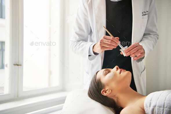 Cosmetologist with brush and woman with mask on face - Stock Photo - Images