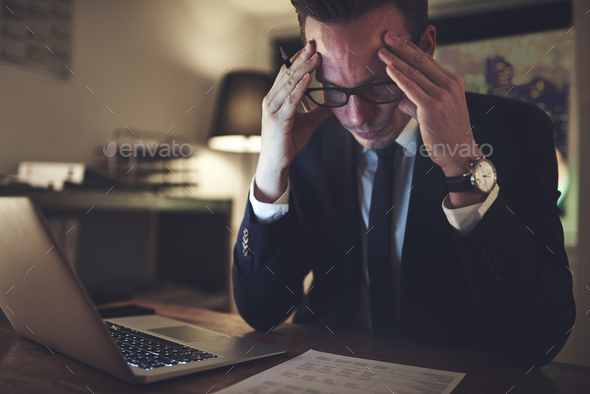 Pensive office worker accounting in the evening - Stock Photo - Images