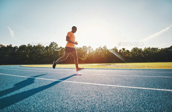 Fit young athlete running along a track in the afteroon - Stock Photo - Images