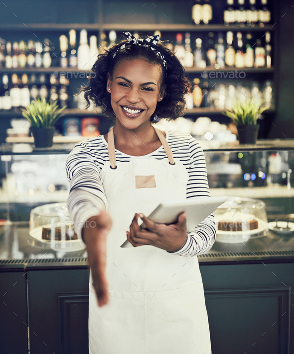 Smiling hostess offering a handshake in a cafe - Stock Photo - Images