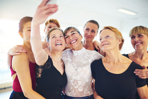 Smiling friends taking selfies together in a dance studio - Stock Photo - Images