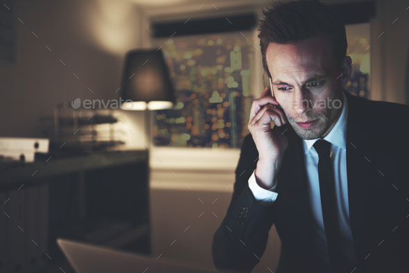 The finance adviser with phone browsing laptop - Stock Photo - Images