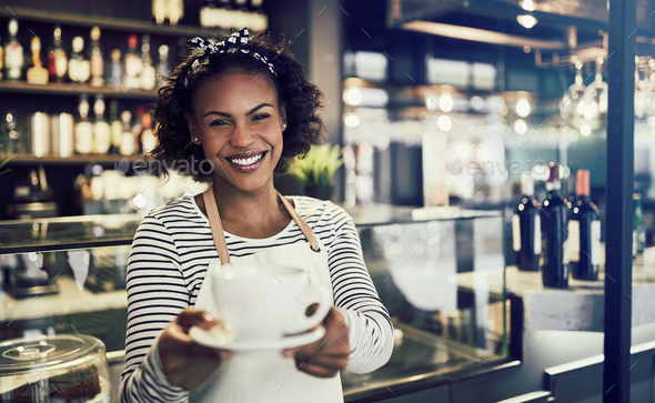 Smiling cafe waitress offering up a cup of fresh coffee - Stock Photo - Images