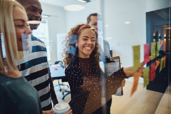 Smiling team of designers having an office brainstorming session - Stock Photo - Images