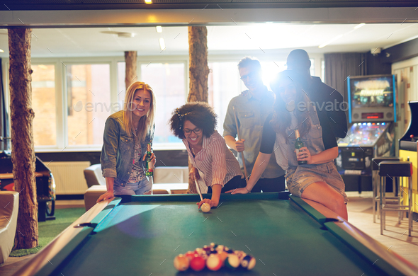 Friends in game room playing pool - Stock Photo - Images