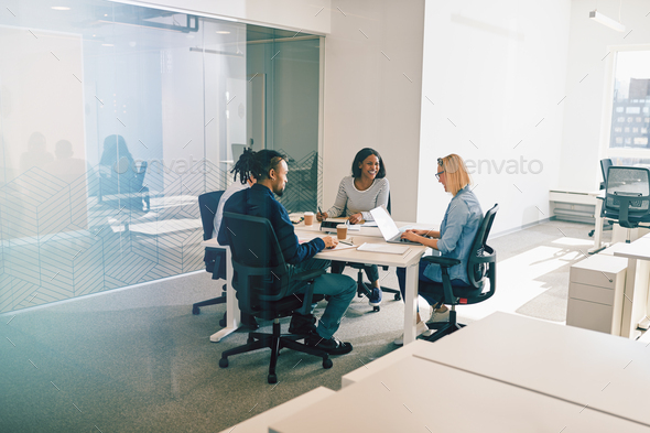 Group of work colleagues laughing during an office meeting together - Stock Photo - Images