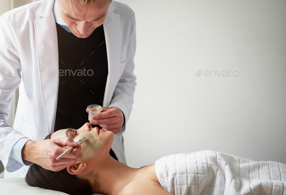 Young cosmetologist putting mask on female face with brush - Stock Photo - Images