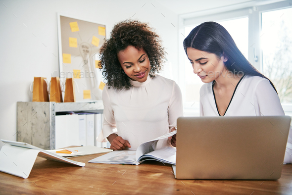 Two young business partners working on paperwork - Stock Photo - Images