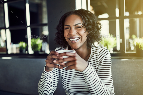 Young African woman laughing and enjoying a cafe coffee - Stock Photo - Images