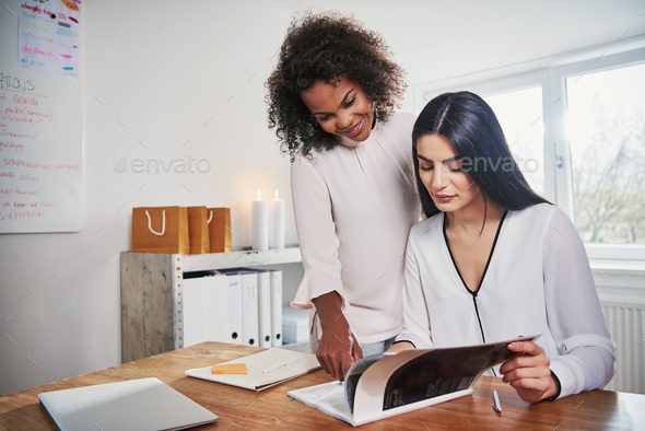 Two women working with documents at workplace - Stock Photo - Images