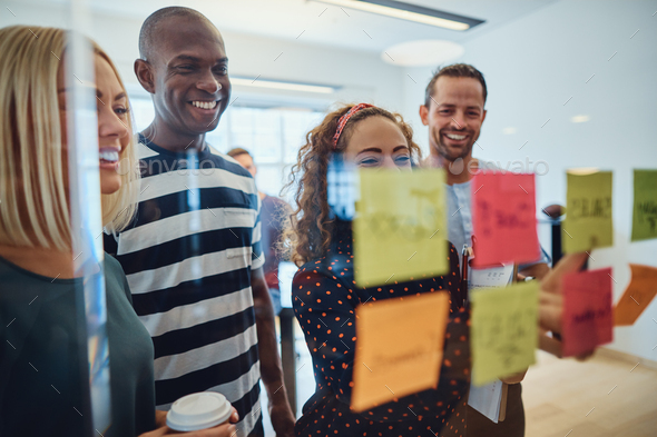 Smiling designers brainstorming on a glass wall in an office - Stock Photo - Images