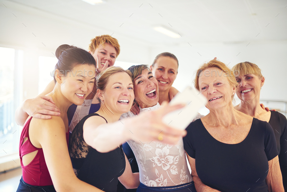 Group of smiling women taking selfies in a dance studio - Stock Photo - Images
