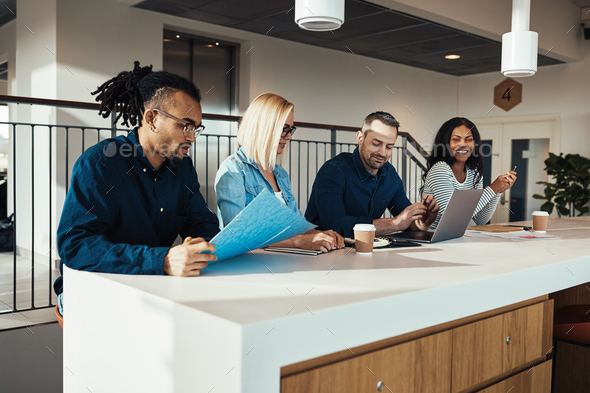 Smiling group of businesspeople discussing work during an office meeting - Stock Photo - Images