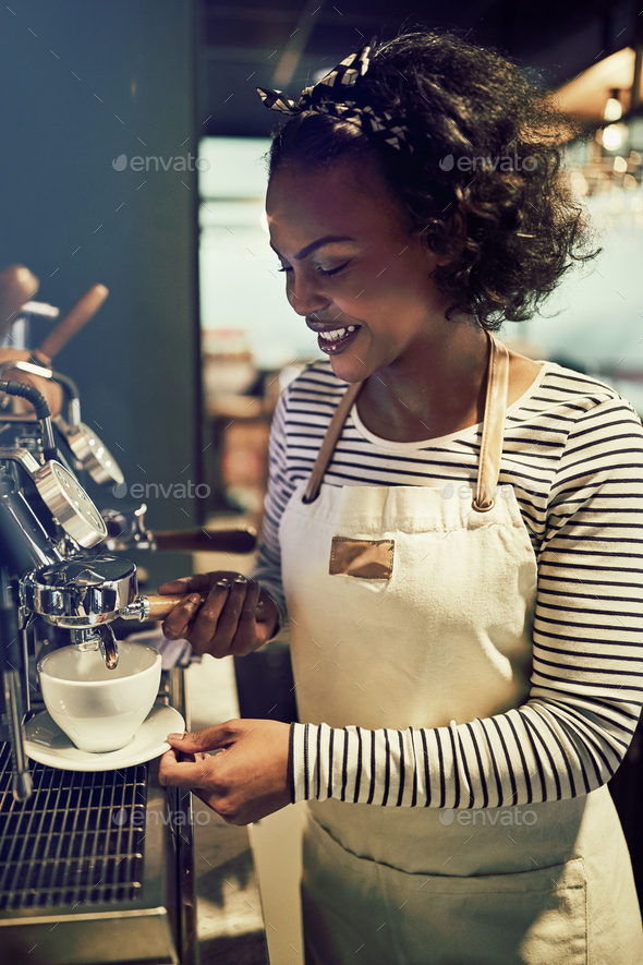 Smiling young African barista making fresh coffee in a cafe - Stock Photo - Images