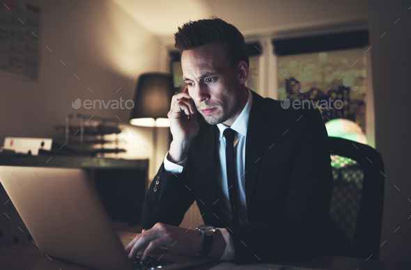 Man browsing laptop and talking the phone - Stock Photo - Images