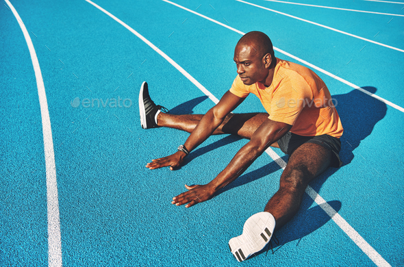 Young runner stretching on a running track before training - Stock Photo - Images