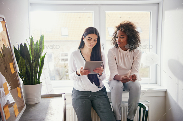 Two pretty young multiracial coworkers browsing tablet - Stock Photo - Images