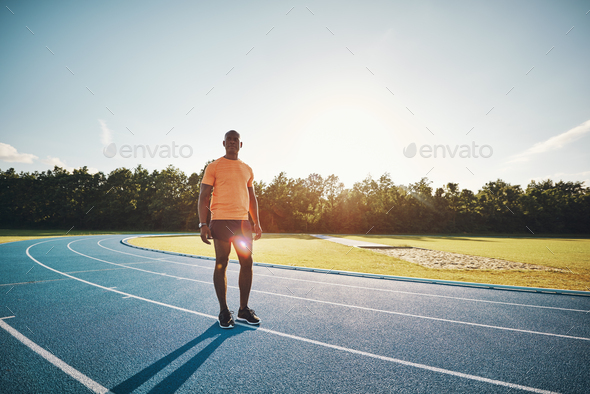 Focused young runner standing alone on a track - Stock Photo - Images