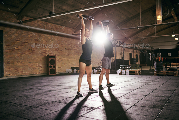 Couple of weightlifters lifting barbells above heads - Stock Photo - Images