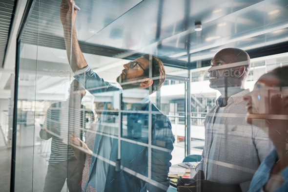 Diverse businesspeople brainstorming on a glass wall in an office - Stock Photo - Images