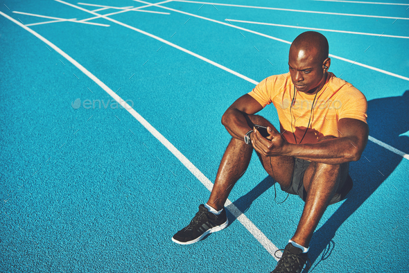Runner sitting alone on an outdoor track listening to music - Stock Photo - Images