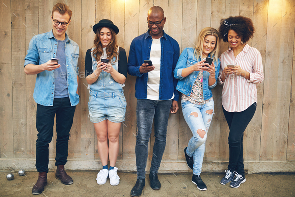 Cheerful multiracial friends messaging with smartphones at wooden wall - Stock Photo - Images