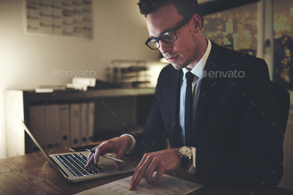 Serious business man working on documents looking concentrated - Stock Photo - Images