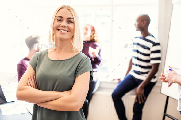 Smiling female designer standing in a bright modern office - Stock Photo - Images