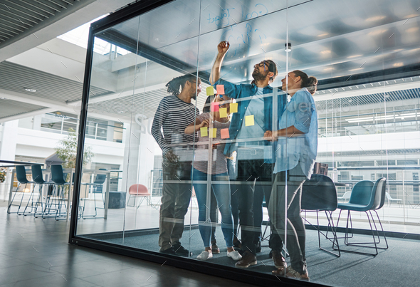 Diverse businesspeople brainstorming together on a glass wall - Stock Photo - Images