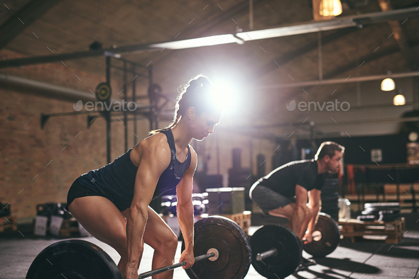 Muscular people doing exercise with heavy barbell - Stock Photo - Images