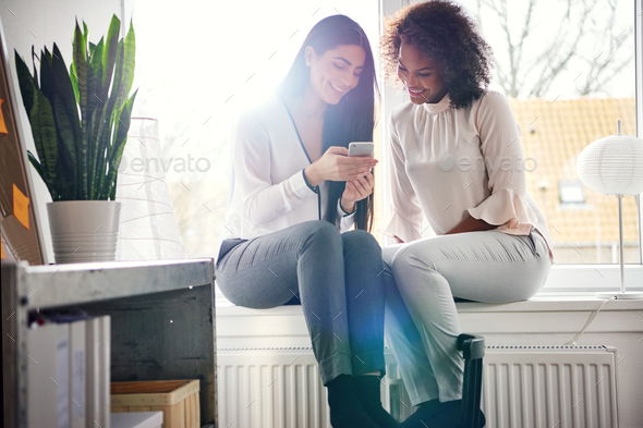 Smiling young women texting a phone message - Stock Photo - Images