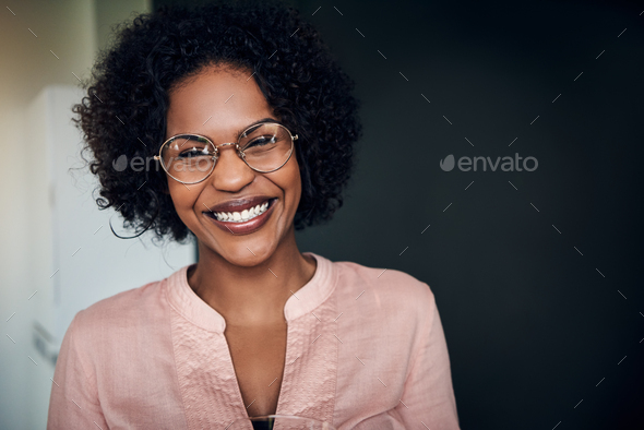 Laughing African businesswoman standing alone in a modern office - Stock Photo - Images