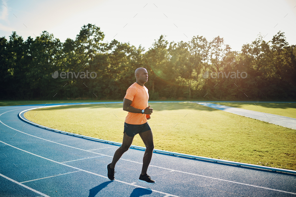 Young athlete running alone on a race track - Stock Photo - Images