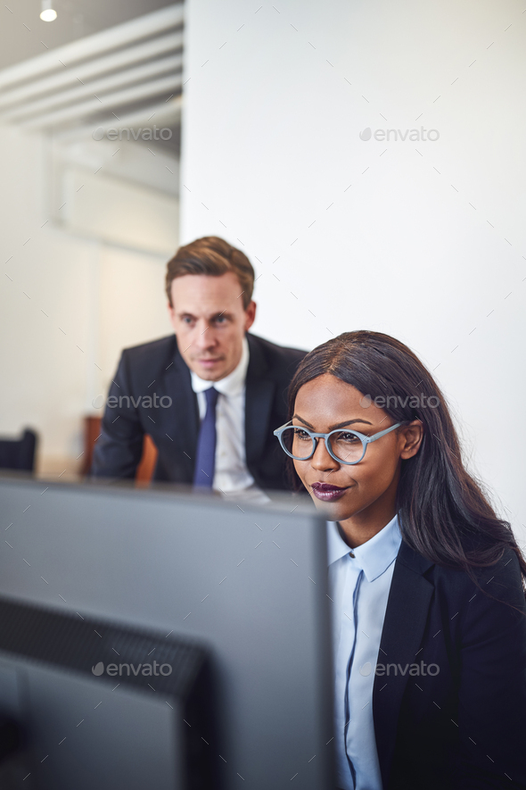 Diverse businesspeople working on a computer together in an office - Stock Photo - Images
