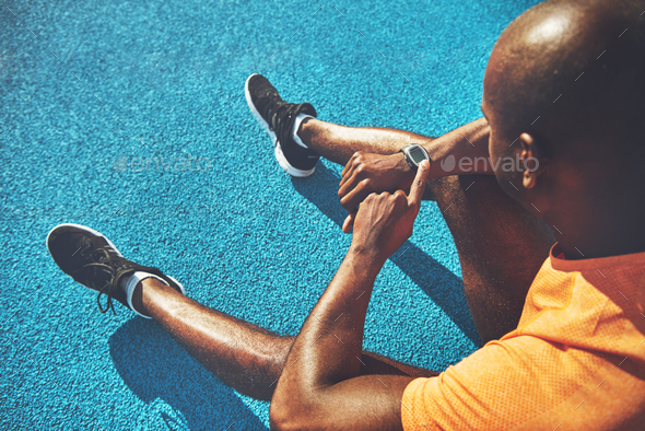 Young runner sitting on a track checking his fitness watch - Stock Photo - Images