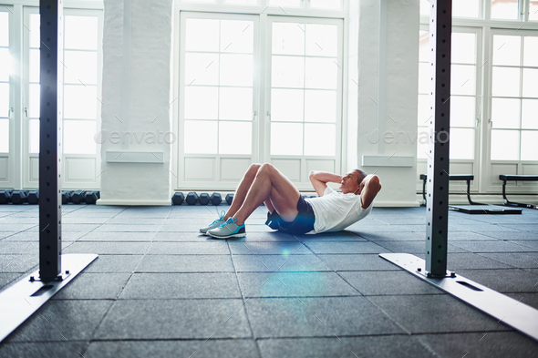 Senior man doing sit ups on a health club floor - Stock Photo - Images
