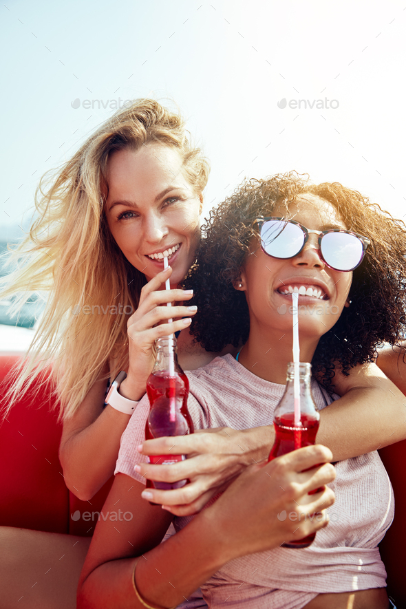 Two smiling young women sitting on a boat sipping drinks - Stock Photo - Images