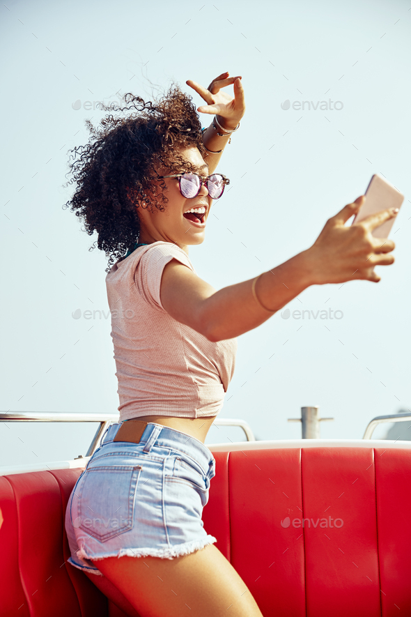 Laughing young woman sitting on a boat taking selfies - Stock Photo - Images