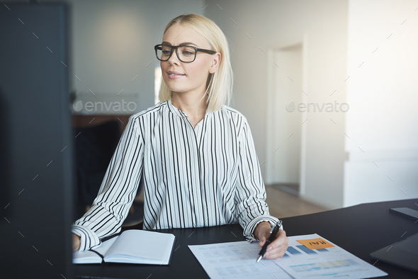 Smiling businesswoman working at her desk in a bright office - Stock Photo - Images