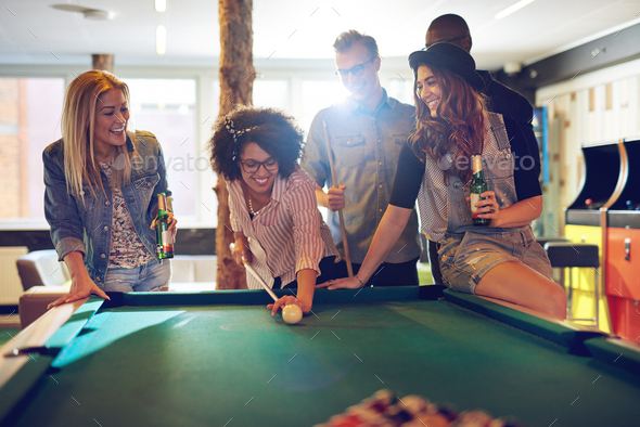 Woman behind the cue ball while friends watch - Stock Photo - Images