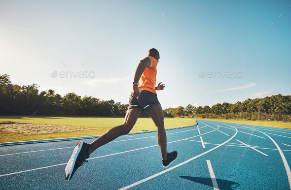 Fit athlete sprinting alone down a running track outside - Stock Photo - Images