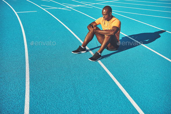 Young African athlete listening to music before a run - Stock Photo - Images