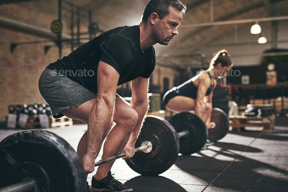 Spotive man and woman lifting heavy barbells - Stock Photo - Images