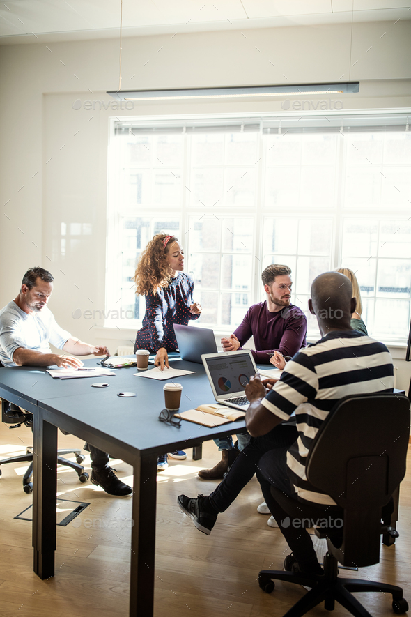 Diverse designers working on a project around an office table - Stock Photo - Images