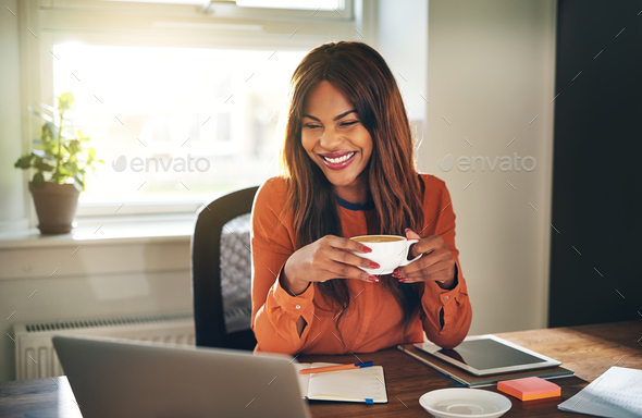 Laughing young woman drinking coffee while working from home - Stock Photo - Images