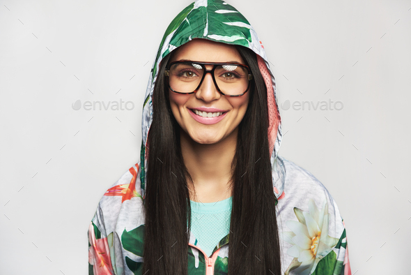 Pretty cheerful female model posing in hood and glasses - Stock Photo - Images