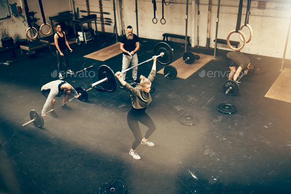 Fit people lifting weights while exercising together in a gym - Stock Photo - Images
