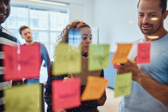 Group of designers brainstorming with notes on a glass wall - Stock Photo - Images